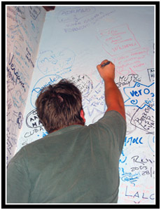 Joe signing his name on the wall of the Bodaguito del Medio (25k image)
