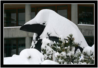 Snow piled high on the Raven sculpture at UAS
